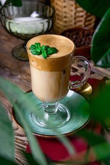 カフェのテーブルにミントの葉で飾られたミルク入りコーヒー、ダルゴナコーヒー、縦の写真。