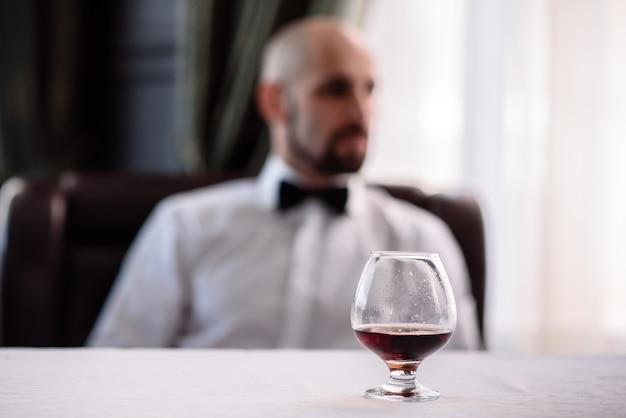 男性の背景にコニャックのグラス。