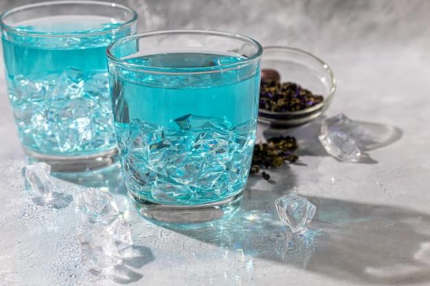 エンドウ豆の花と氷を入れた冷たいブルーティーのグラス。ブルーピース。健康的な飲酒のために、体を解毒します。灰色のテーブル。