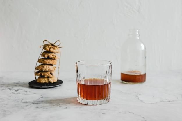 Стакан холодного кофе, стопка овсяного печенья