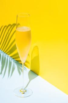 太陽の光の夏のコンセプトからココナッツの葉の影を持っている蒸気と冷たいシャンパンのガラス