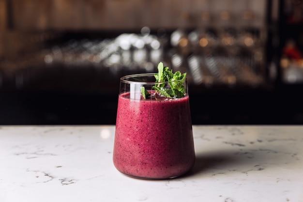 민트 장식, 대리석 테이블로 장식된 차가운 숲 과일 베리 스무디 칵테일 한 잔.