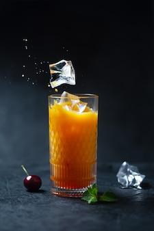 Стакан холодного апельсинового сока с ягодами вишни и летающим льдом на темном фоне. низкий ключ