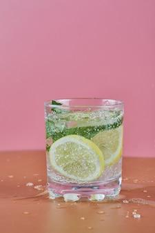 분홍색 표면에 차가운 상쾌한 레모네이드 한 잔