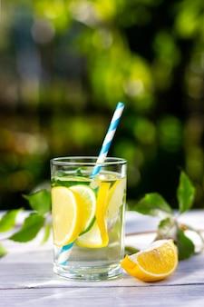 夏の晴れた日にストローと冷たい飲み物と一緒に冷たいレモネードのグラス