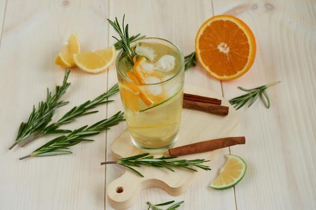 Стакан прохладного лимонада с цитрусовыми и розмарином, корицей на деревянном столе