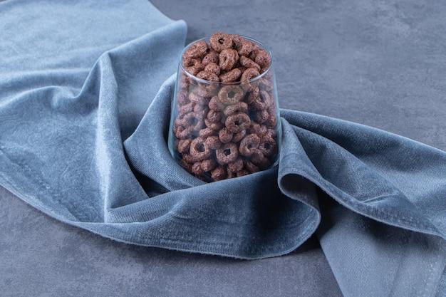 파란색 배경에 직물 조각에 옥수수 반지 한 잔. 고품질 사진