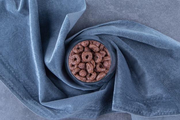 파란색 배경에 직물 조각에 옥수수 반지 한 잔.