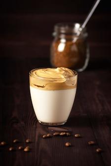 달고나 커피 한 잔과 인스턴트 커피 캔이 어두운 나무 테이블 위에 놓여 있습니다.
