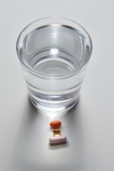 コップ1杯の飲料水といくつかのビタミン入りカプセル。明るい背景。閉じる。