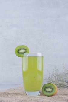 黄麻布に新鮮なキウイジュースのグラス。高品質の写真