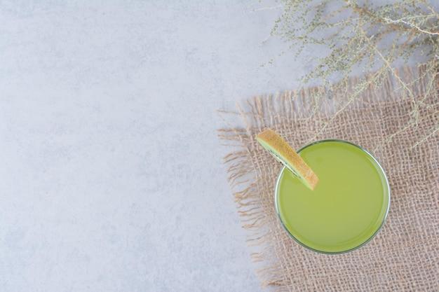 黄麻布に新鮮なキウイジュースのグラス。