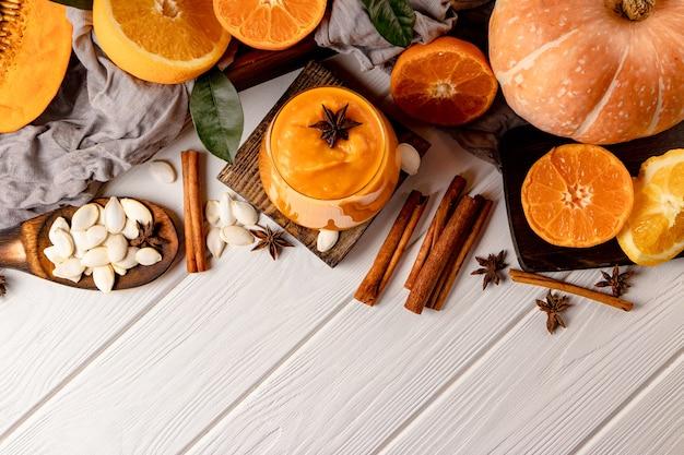Стакан свежей тыквы и апельсина со специями на столе. свободное место для вашего текста. фото высокого качества