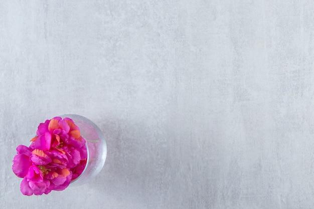흰색 테이블에 신선한 보라색 꽃의 유리.