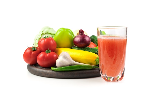 Стакан свежевыжатого овощного сока и большой выбор свежих овощей на круглом подносе.