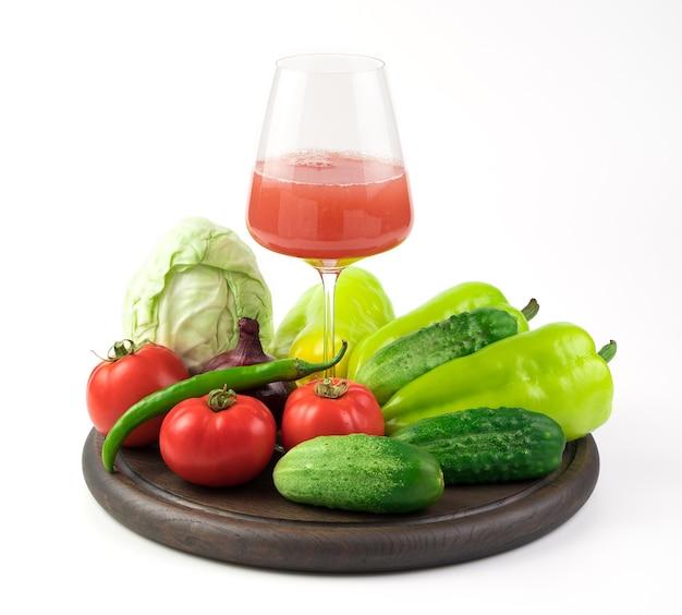 Стакан свежевыжатого овощного сока и большой выбор свежих овощей на круглом подносе. понятие о правильном питании.