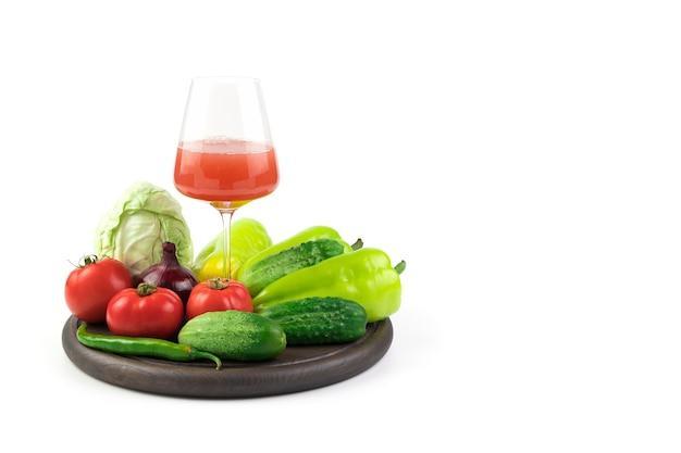 Стакан свежевыжатого овощного сока и свежих овощей на круглом подносе. понятие о правильном питании.