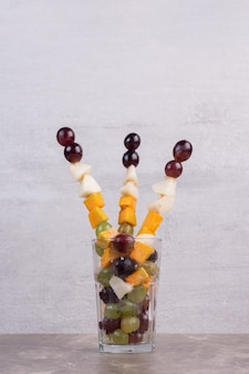 白いテーブルの上の果物のガラス。