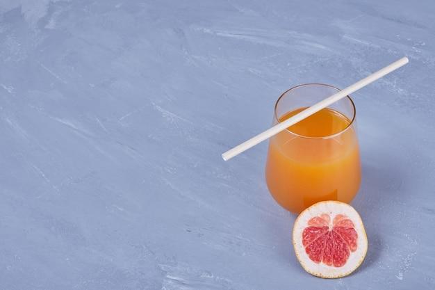 パイプ付きグレープフルーツジュースのグラス。