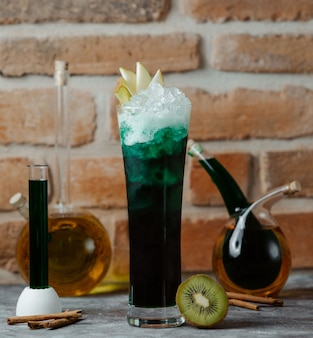 Стакан зеленого алкоголя коктейль с кусочками яблок и кубиками льда.