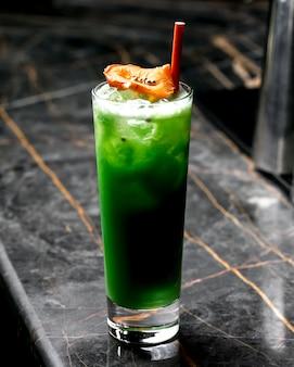 말린 오렌지와 붉은 종이 짚으로 장식 된 녹색 칵테일 한 잔
