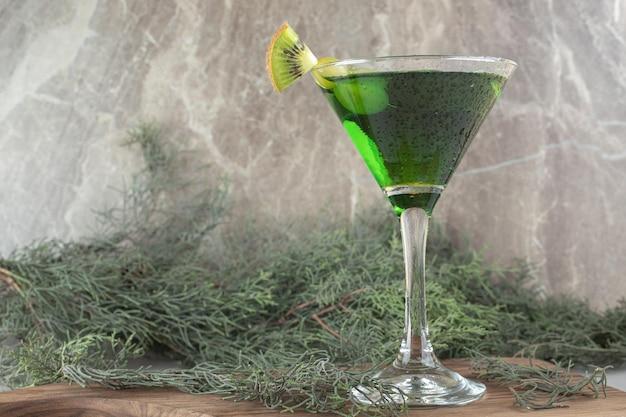 Стакан зеленого коктейля с кусочками киви на деревянной доске