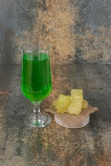 大理石の壁に黄色い砂糖のスライスと緑のレモネードのガラス。