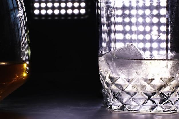 バーカウンターに氷とハードアルコールのグラス。グラスにソーダを入れたウイスキー。アルコール飲料の宣伝。