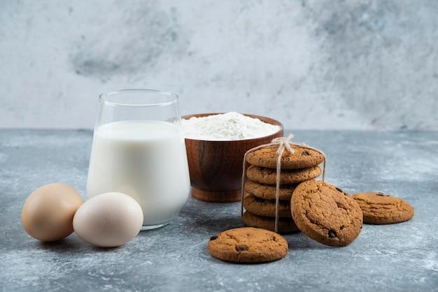 Стакан горячего молока с вкусным печеньем на сером столе.