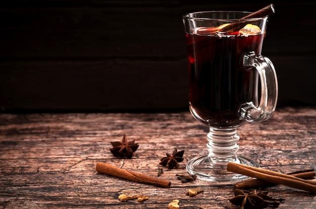 コピースペースと暗いヴィンテージの木製スペースにシナモンスティックとレモンのスライスとホットホットワインのグラス