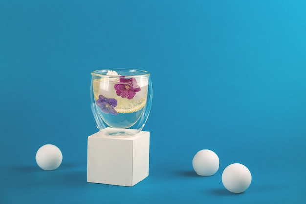 モダンなスタイルの食用スミレの花で飾られた氷水のガラス