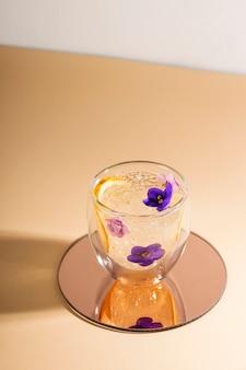 둥근 거울에 꽃으로 장식 된 얼음 물 한잔