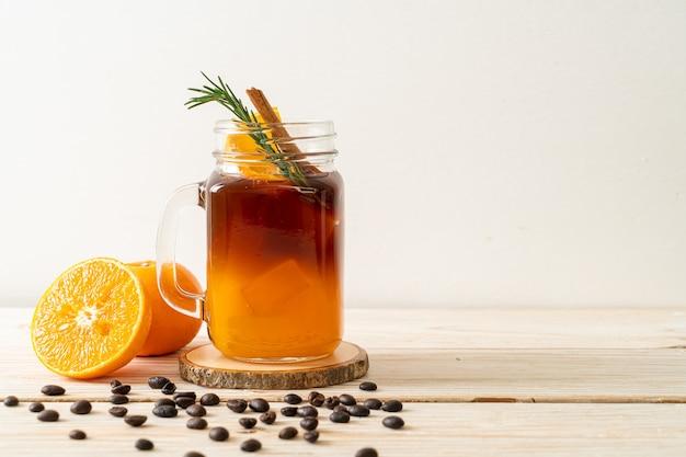 Стакан черного кофе американо со льдом и слой апельсинового и лимонного сока, украшенный розмарином и корицей на деревянном фоне