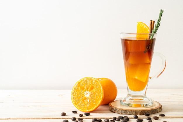 Стакан черного кофе американо со льдом и слой апельсинового и лимонного сока, украшенный розмарином и корицей на деревянной поверхности