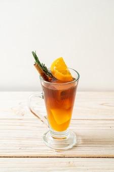 아이스 아메리카노 블랙 커피 한잔과 나무 표면에 로즈마리와 계피로 장식 된 오렌지와 레몬 주스의 층