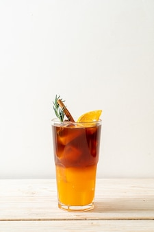 아이스 아메리카노 블랙 커피 한잔과 나무 테이블에 로즈마리와 계피로 장식 된 오렌지와 레몬 주스의 층