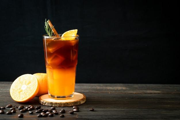 Стакан черного кофе американо со льдом и слой апельсинового и лимонного сока, украшенный розмарином и корицей
