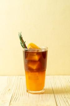 아이스 아메리카노 블랙 커피 한잔과 로즈마리와 계피로 장식 된 오렌지와 레몬 주스 층