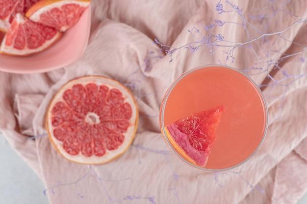 Стакан сока и свежий грейпфрут на розовой ткани