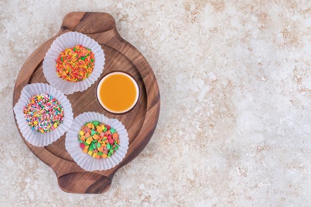 ボード上の小さなキャンディーの山で満たされたパティケースの横にあるジュースのグラス