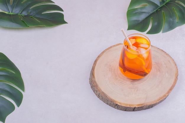 中に柑橘系の果物が入ったジュースのグラス