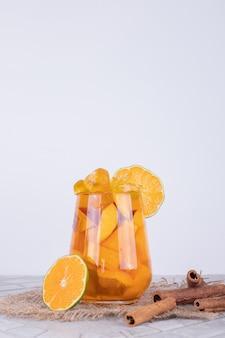 Стакан сока с кусочками фруктов и корицей.