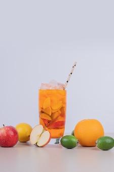 Стакан сока с кусочками фруктов и свежими фруктами.