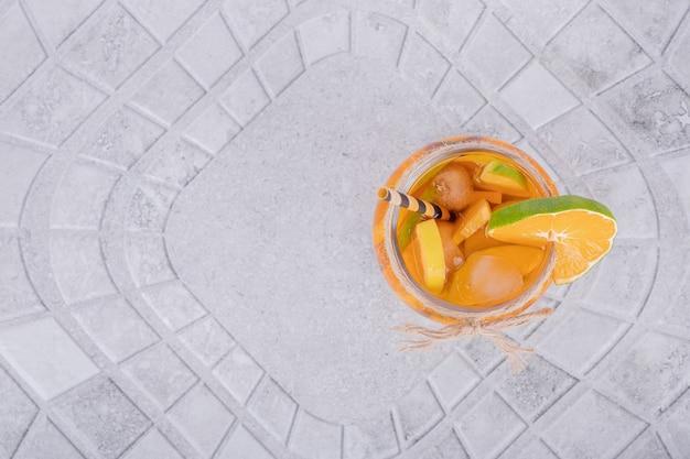 大理石のテーブルにフルーツスライスとジュースのガラス。
