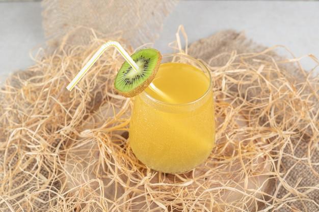 黄麻布にキウイスライスとストローを添えたジュースのグラス。