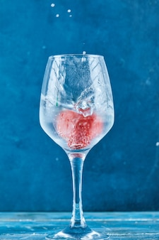파란색 표면에 내부 딸기 주스 한 잔