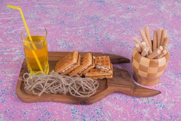 Стакан сока с вафлями на деревянном блюде и в деревянной чашке