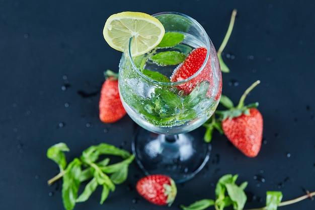 暗い表面にフルーツ全体とレモンのスライスが入ったジュースのグラス