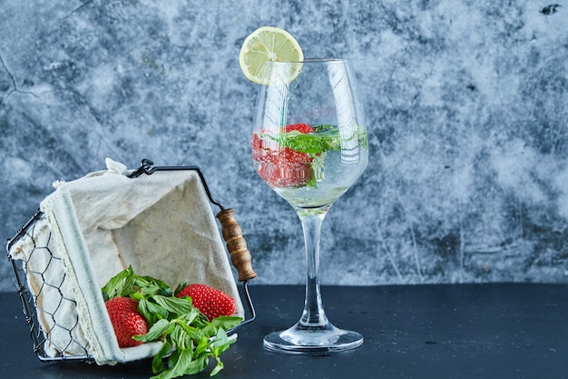 Стакан сока с целыми фруктами внутри и корзина с клубникой на синей поверхности
