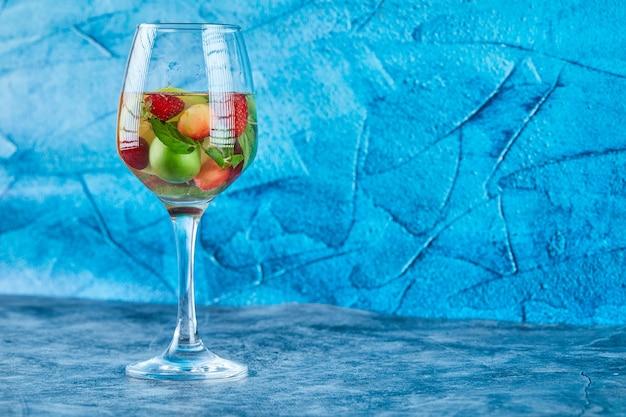 青い表面に果物全体が入ったジュースのグラス
